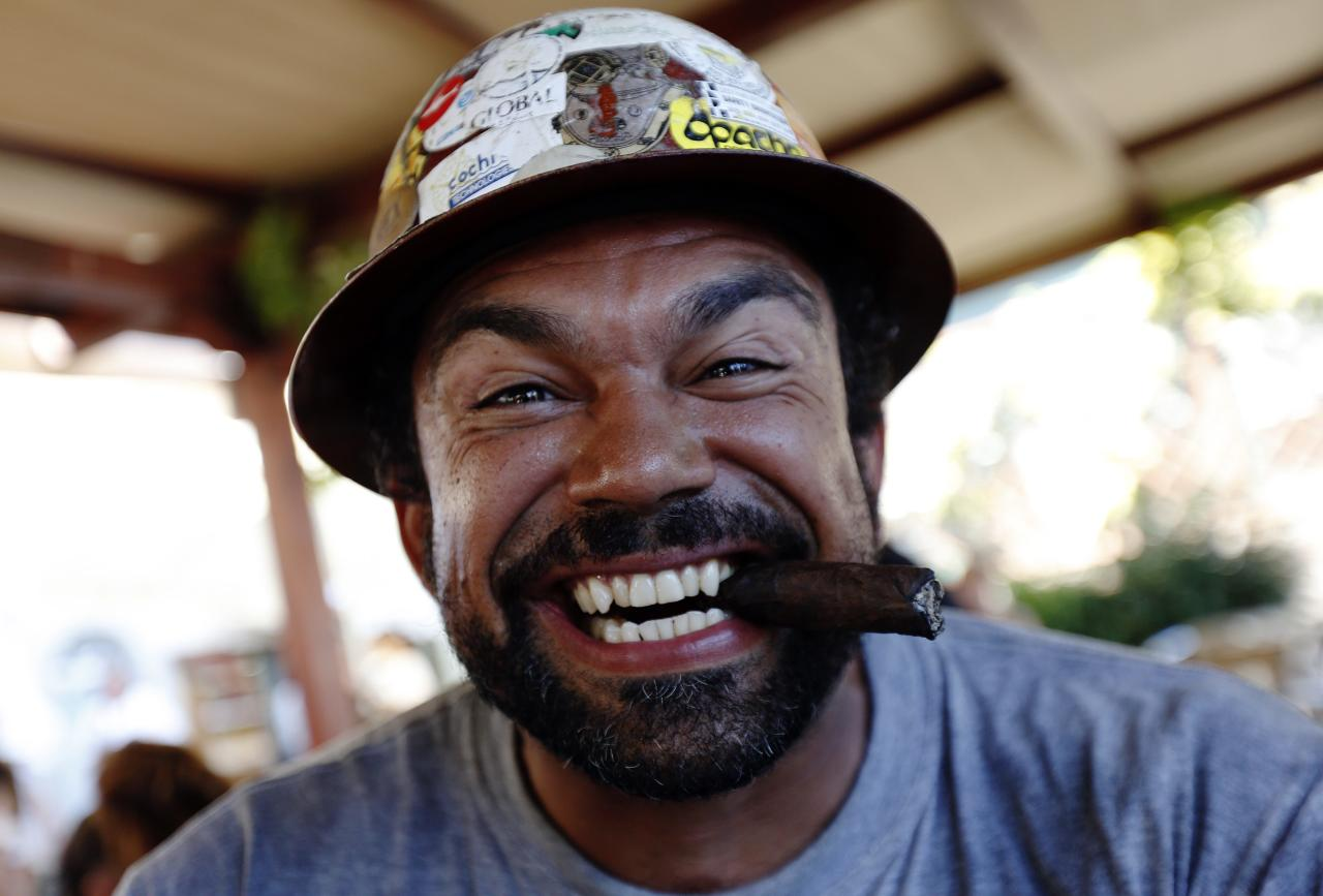 A Dutch salvage worker smokes cigar as he celebrates after the refloat operation maneuvers that allowed cruise liner Costa Concordia to leave Giglio Island July 23, 2014. Maneuvers began early on Wednesday to remove the rusty hulk of the Costa Concordia cruise liner from the Italian island where it struck rocks and capsized two years ago, killing 32 people. A convoy of 14 vessels, led by the tug boat Blizzard, will start to tow the Concordia later on Wednesday to a port near Genoa in northern Italy where it is due to arrive on Sunday, before being broken up for scrap. REUTERS/Max Rossi ( ITALY - Tags: DISASTER TRANSPORT MARITIME SOCIETY)