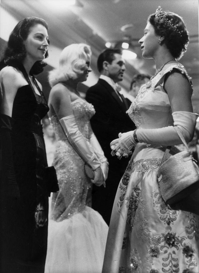 <p>Queen Elizabeth chatted with screen star Ava Gardner at the premiere of <em>To Catch a Thief, </em>and the actress looked impossibly chic in a black evening gown and matching gloves. But what we really want to know is where did QE2 get that gorgeous embroidered gown?</p>