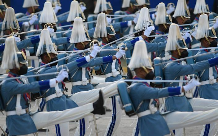 A masked Air Force cadets march during a military parade marking Independence Day in Caracas, Venezuela - Matias Delacroix/AP