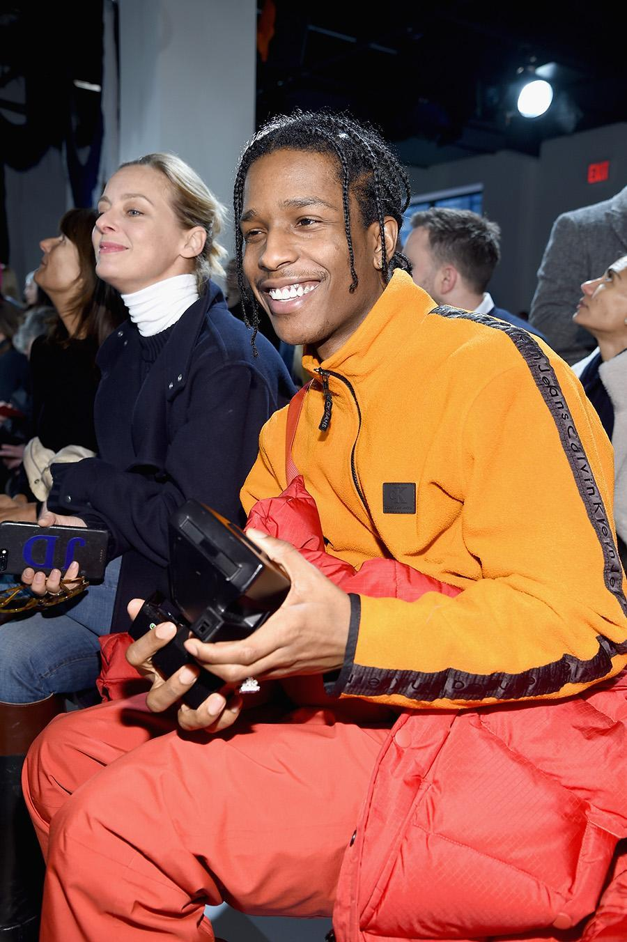 <p>Rapper A$AP Rocky wore an orange jacket that featured the name of the label on the sleeves to the show. (Photo: Getty Images) </p>