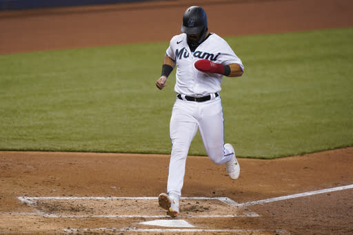 Miami Marlins' Jorge Alfaro scores on a single by Starling Marte during the third inning of the first game of a baseball doubleheader against the Philadelphia Phillies, Sunday, Sept. 13, 2020, in Miami. (AP Photo/Wilfredo Lee)