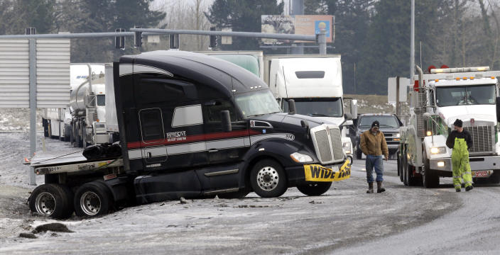 Truck driver Brad Cottle, left, from Florida, surveys the situation with his truck stuck in a ditch with tow truck driver Donny Callahan in Troutdale, Ore., Wednesday, Jan. 18, 2017. An ice storm shut down parts of major highways and interstates Wednesday in Oregon and Washington state and paralyzed the hardest hit towns along the Columbia River Gorge with up to 2 inches of ice coating the ground in some places.(AP Photo/Don Ryan)
