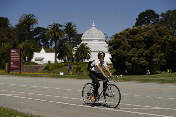 A woman on a bicycle rides along the car-free John F. Kennedy Drive in Golden Gate Park with the Conservatory of Flowers in the background, Wednesday, April 28, 2021, in San Francisco. At the start of the pandemic, San Francisco closed off parts of a major beachfront highway and Golden Gate Park to cars so that people had a safe place to run and ride bikes. Open space advocates want to keep those areas car-free as part of a bold reimagining of how U.S. cities look. But opponents decry the continued closures as elitist, unsafe and nonsensical now that the pandemic is over and people need to drive again. (AP Photo/Eric Risberg)