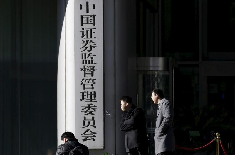 Men rest outside the headquarters building of China Securities Regulatory Commission in Beijing