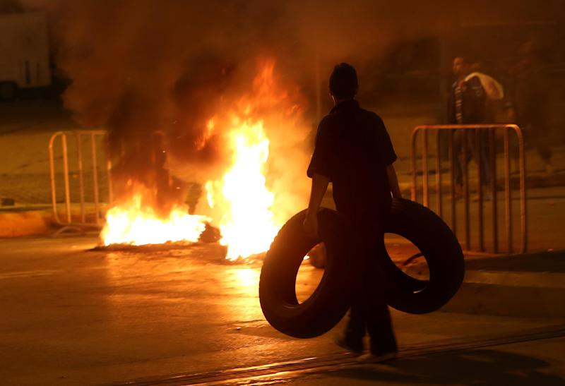 A Sunni protestor carries tires as a fire set by Sunni protesters burns on a major roadway between Beirut and the capital's southern suburbs, a Hezbollah stronghold, to show support for residents of the Sunni town of Arsal, in Beirut, Lebanon, Tuesday, March 18, 2014. Gunmen from Lebanon's militant Hezbollah group and local Shiite Muslim residents tightened their blockade of a Sunni town of Arsal near the Syrian border Tuesday, sparking concerns that thousands of Syrian refugees stranded in the area could be cut off from humanitarian aid. (AP Photo/Hussein Malla)