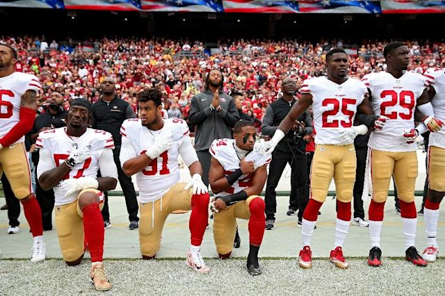 Football players from the San Francisco 49ers protest by kneeling during the national anthem (AFP Photo/Patrick Smith)
