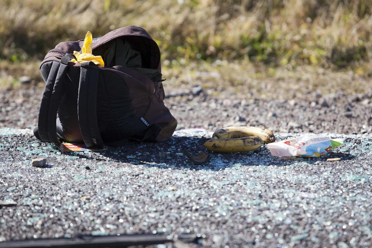 A backpack lies on a road after a minivan crashed, near Turangi, New Zealand, Saturday, May 12, 2012. Three Boston University students who were studying in New Zealand were killed Saturday when their minivan crashed. At least five other students from the university were injured in the accident, including one who was in critical condition. (AP Photo/New Zealand Herald, John Cowpland) NEW ZEALAND OUT, AUSTRALIA OUT