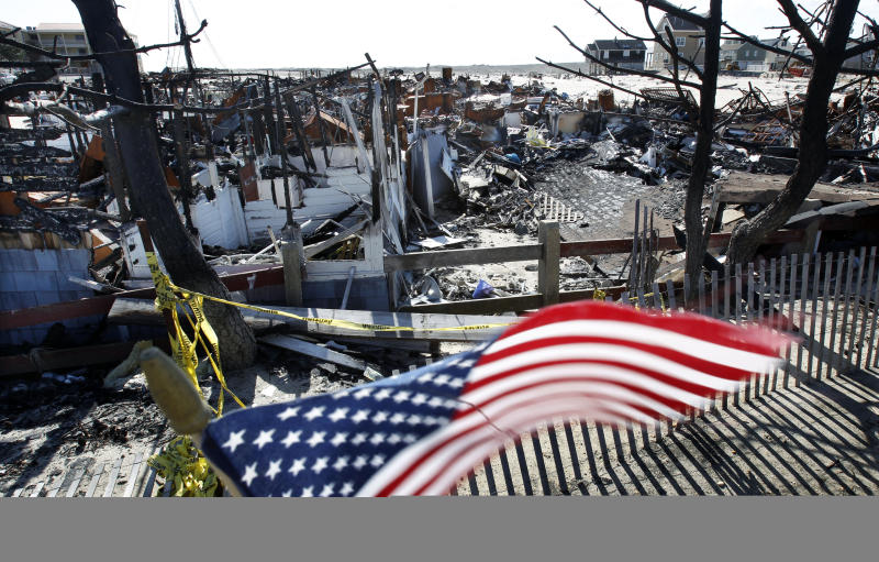 Flags decorate a fence Thursday, April 25, 2013, in Brick, N.J., around the burned remains of more than 60 small bungalows at Camp Osborn which were destroyed last October during Superstorm Sandy. Six months after Sandy devastated the Jersey shore and New York City and pounded coastal areas of New England, the region is dealing with a slow and frustrating, yet often hopeful, recovery. (AP Photo/Mel Evans)