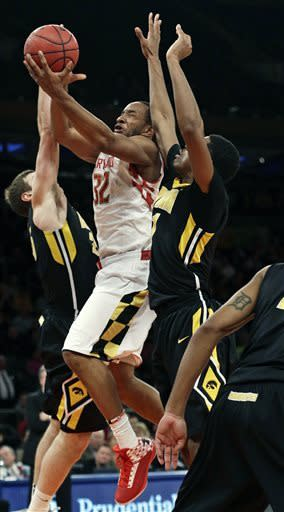 Maryland's Dez Wells (32) drives past Iowa's Melsahn Basabe, right, and Eric May, left, during the first half of an NIT semifinal basketball game Tuesday, April 2, 2013, in New York. (AP Photo/Frank Franklin)