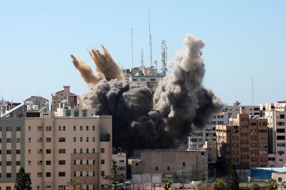 A thick column of smoke rises from the al-Jalaa Tower as it is destroyed in an Israeli airstrike in Gaza City controlled by the Palestinian Hamas movement.