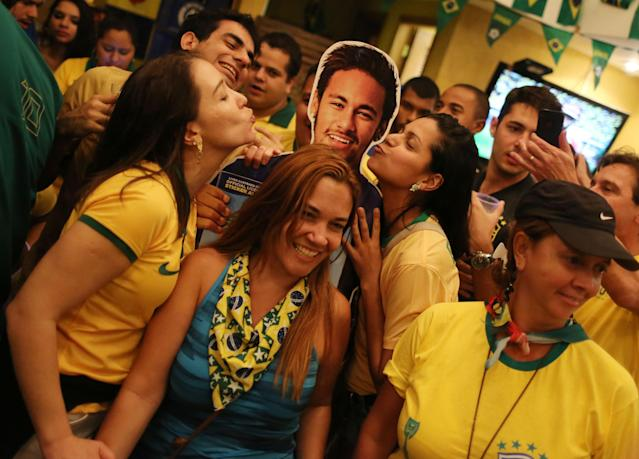Soccer fans donning Brazil's national team colors pose for a picture with a life-size cutout of soccer star Neymar, after the World Cup match between Brazil and Cameroon, at the Copacabana beach, in Rio de Janeiro, Brazil, Monday, June 23, 2014. Neymar lived up to the expectations of the World Cup host nation Monday, scoring two goals as Brazil routed Cameroon 4-1 to reach the knockout stage as the top team in Group A. (AP Photo/Leo Correa)