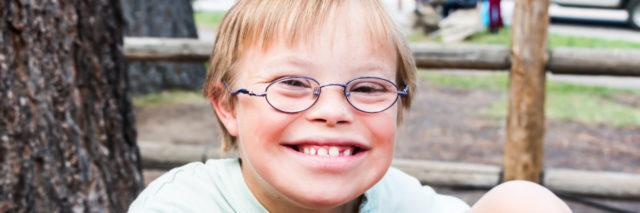 Cute little boy with Down syndrome sitting at a picnic table.