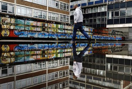 """A man passes graffiti near the Old Street roundabout dubbed """"Silicon Roundabout"""" in London May 28, 2013 in this May 28, 2013 file photo.  REUTERS/Luke Macgregor/Files"""