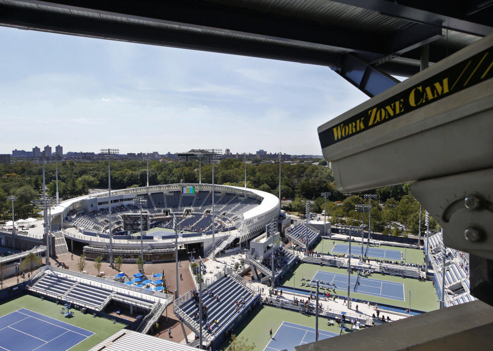 FILE - In this Aug. 24, 2016, file photo, a closed circuit construction camera peers out at the Grandstand stadium during qualifying rounds at the Billie Jean King National Tennis Center in New York. Nascent forms of crowd monitoring — like laser-driven density detection and camera-based line-length calculations — will likely grow faster in a post-pandemic era of live sports, (AP Photo/Kathy Willens, File)
