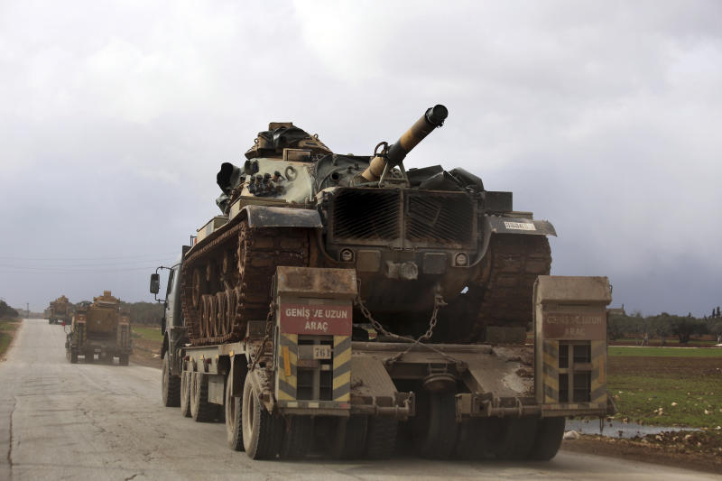 Turkish military convoy drives through the village of Binnish, in Idlib province, Syria, Saturday, Feb. 8, 2020. Several Turkish armored vehicles and tanks entered rebel-controlled northwestern Syria since Friday, the latest reinforcements sent in by Ankara amid a Syrian government offensive that this week brought the two countries' troops into a rare direct confrontation. (AP Photo/Ghaith Alsayed)