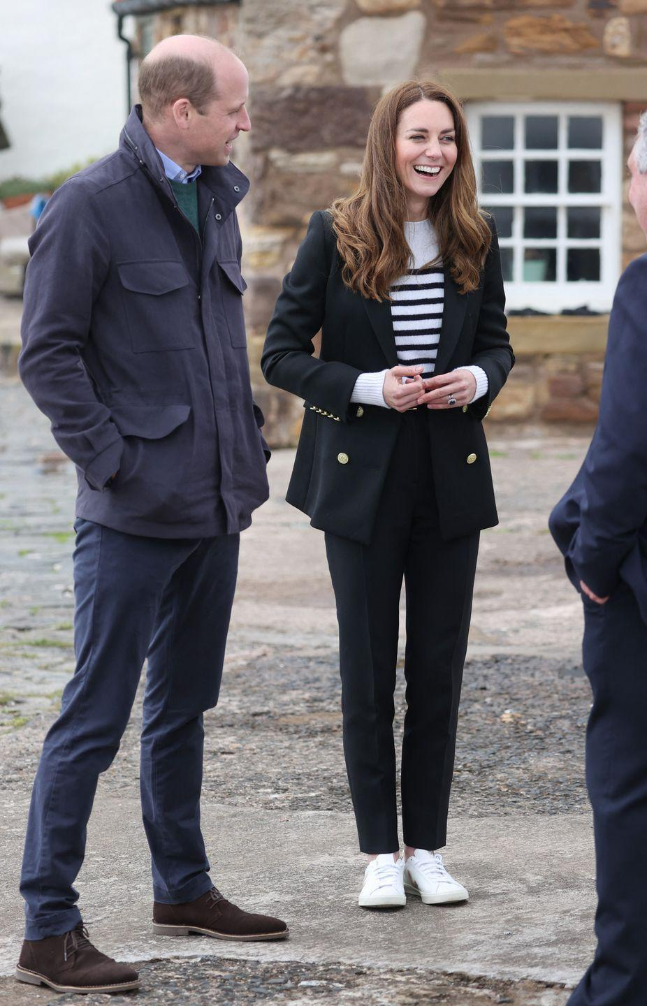 """<p>Meeting with fishermen in St Andrews, Scotland, the Duchess of Cambridge chose an appropriate nautical-inspired sweater, paired with a black blazer and slacks. She finished off the polished look with <a href=""""https://www.townandcountrymag.com/style/fashion-trends/g15925659/kate-middleton-favorite-shoes/"""" rel=""""nofollow noopener"""" target=""""_blank"""" data-ylk=""""slk:Veja sneakers"""" class=""""link rapid-noclick-resp"""">Veja sneakers</a>, a longtime Meghan Markle staple shoe.</p><p><a class=""""link rapid-noclick-resp"""" href=""""https://go.redirectingat.com?id=74968X1596630&url=https%3A%2F%2Fwww.net-a-porter.com%2Fen-us%2Fshop%2Fproduct%2Fveja%2Fshoes%2Flow-top%2Fplus-net-sustain-esplar-metallic-trimmed-leather-sneakers%2F22527730566102805&sref=https%3A%2F%2Fwww.townandcountrymag.com%2Fstyle%2Ffashion-trends%2Fnews%2Fg1633%2Fkate-middleton-fashion%2F"""" rel=""""nofollow noopener"""" target=""""_blank"""" data-ylk=""""slk:Shop the Sneakers"""">Shop the Sneakers</a></p>"""