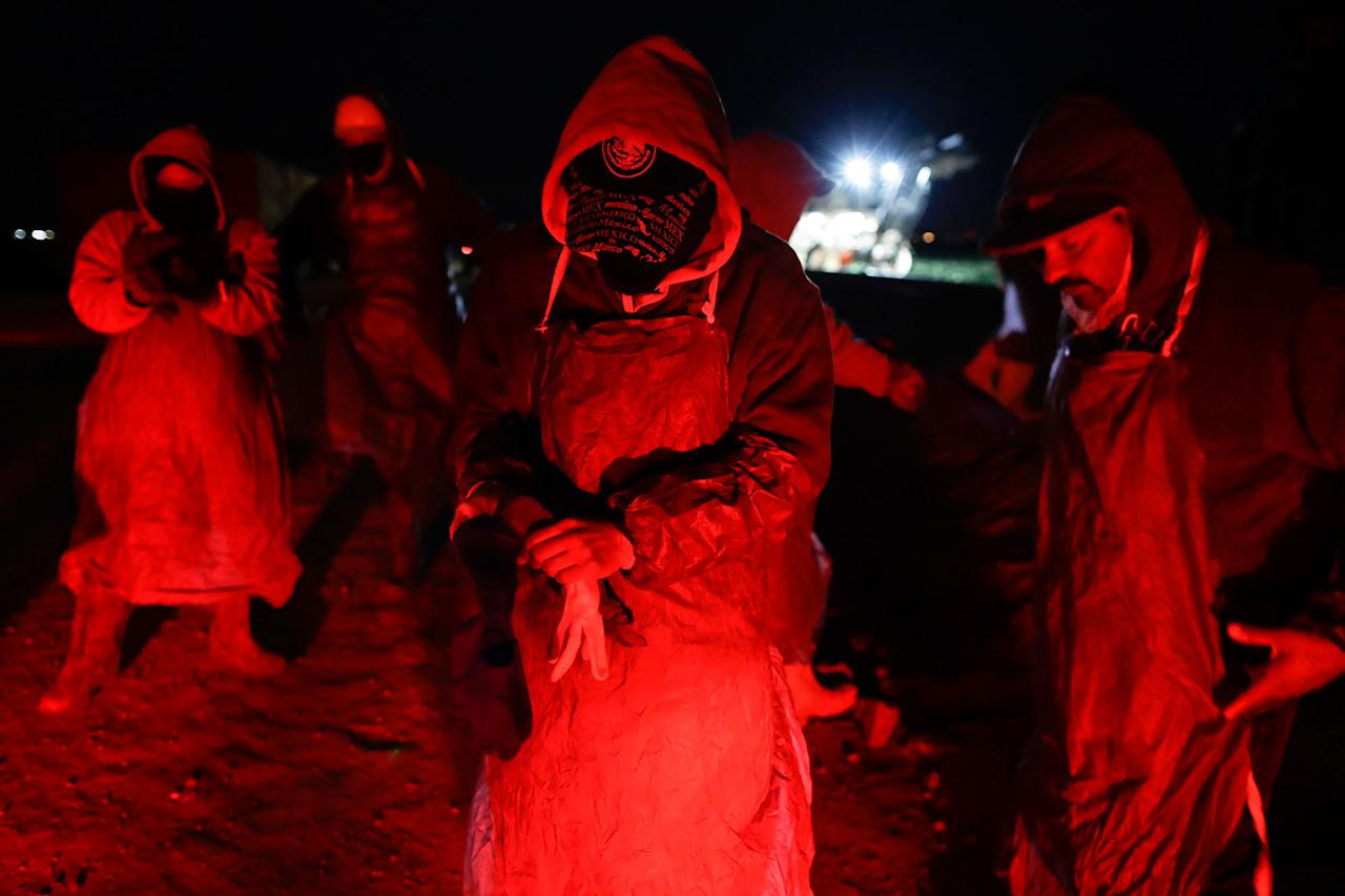 <p>Farmworker Eduardo Garcia, of Mexicali, Mexico, center, puts on an apron and gloves in the glow from the taillights of a bus, as he and his crew arrive at a cabbage field ready for harvest, before dawn outside of Calexico, Calif., March 6, 2018. (Photo: Gregory Bull/AP) </p>