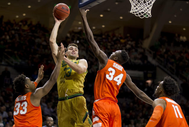 Notre Dame's John Mooney (33) goes up for a shot between Syracuse's Elijah Hughes (33), Bourama Sidibe (34) and Oshae Brissett (11) during the second half of an NCAA college basketball game Saturday, Jan. 5, 2019, in South Bend, Ind. Syracuse won 72-62. (AP Photo/Robert Franklin)