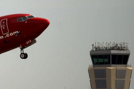 FILE PHOTO: Norwegian aircraft takes off past the air traffic control tower of Pablo Ruiz Picasso Airport in Malaga