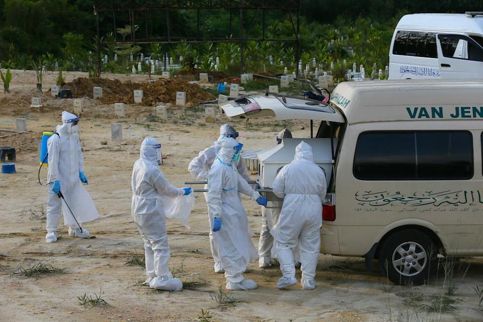 Covid 19 victims body arrive for funeral service handled by health workers equipped with personal protective suit at Kampung Sungai Pusu muslim cemetery May 22,2021.— Picture by Ahmad Zamzahuri