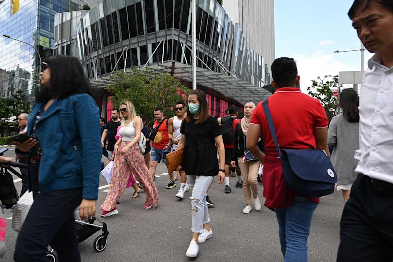 A woman wearing a protective facemask amid fears about the spread of the COVID-19 coronavirus crosses the road in Singapore on February 26, 2020. (Photo by ROSLAN RAHMAN / AFP) (Photo by ROSLAN RAHMAN/AFP via Getty Images)