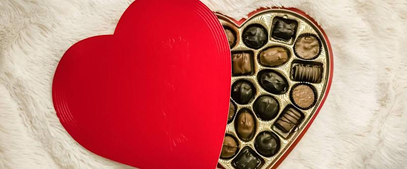 A high-angle view of a heart-shaped box with chocolates on a white fur blanket