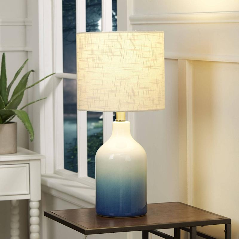 """For a pop of color, you could go with this blue ombre lamp, which is supposed to blend well with <a href=""""https://www.huffpost.com/entry/bohemian-furniture-and-home-decor_n_59e7a9e0e4b00905bdae6e54"""" target=""""_blank"""" rel=""""noopener noreferrer"""">bohemian decor</a> (especially anything rattan). It features a ceramic base andwhite lamp shade. You'll have to get a60-watt or3-watt CGL bulb.<a href=""""https://fave.co/3bZEoym"""" target=""""_blank"""" rel=""""noopener noreferrer"""">Find it for $30 at Walmart</a>."""