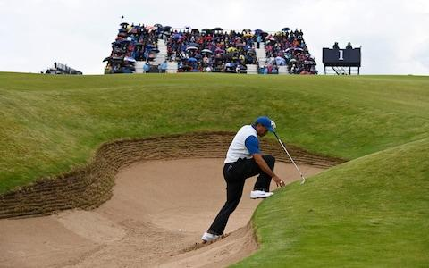 Woods climbing out of a bunker - Credit: R&A