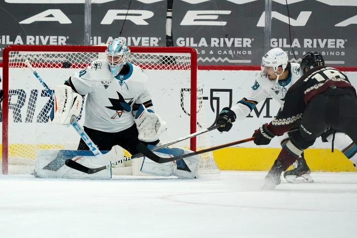 San Jose Sharks goaltender Martin Jones (31) makes a save on a shot from Arizona Coyotes center Derick Brassard (16) as Sharks defenseman Mario Ferraro (38) pressures Brassard during the second period of an NHL hockey game Saturday, Jan. 16, 2021, in Glendale, Ariz. (AP Photo/Ross D. Franklin)