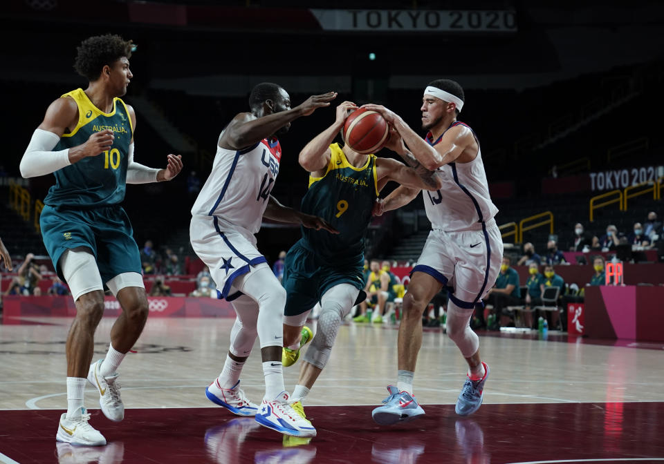 Australia's Nathan Sobey (9) second right, drives between United States's Devin Booker (15), right, and United States's Draymond Green (14) during men's basketball semifinal game at the 2020 Summer Olympics, Thursday, Aug. 5, 2021, in Saitama, Japan. (AP Photo/Charlie Neibergall)