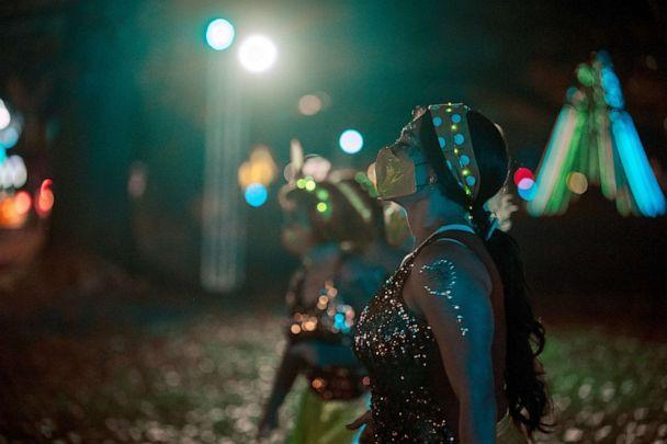 PHOTO: Dancers in the Roux La La krewe perform for vehicles driving by during the Mardi Gras Float in the Oaks event in City Park, Feb. 14, 2021, in New Orleans, Louisiana. (Jon Cherry/Getty Images)