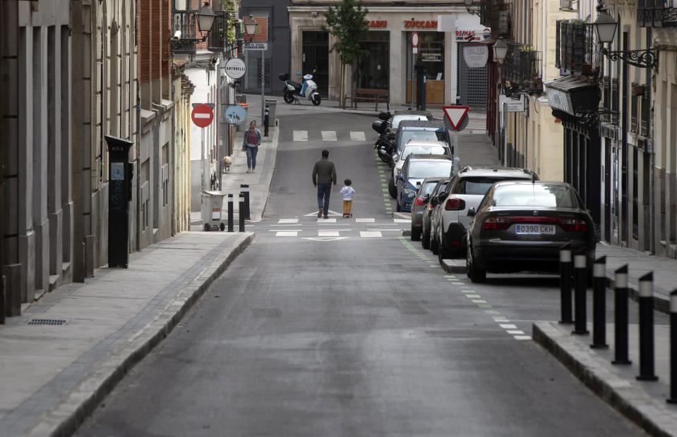 A man takes a young boy for a walk in Madrid, Spain, Sunday, April 26, 2020. On Sunday, children under 14 years old are allowed to take walks with a parent for up to one hour and within one kilometer from home, ending six weeks of compete seclusion due to the coronavirus outbreak. (AP Photo/Paul White)