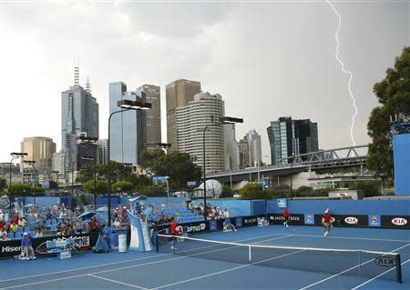 A bolt of lightning appears in the sky as Stephane Robert of France plays Michal Przysiezny of Poland during their men's singles match at the Australian Open 2014 tennis tournament in Melbourne January 16, 2014. REUTERS/Brandon Malone