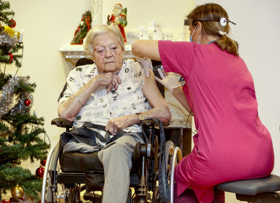 Nurse Ann-Louise Broberg injects a COVID-19 vaccine to nursing home resident Gun-Britt Johnsson in Mjolby, Sweden, Sunday, Dec. 27, 2020. Gun-Britt was the first in Sweden to receive the vaccine. (Stefan Jerrevang/TT News Agency via AP)