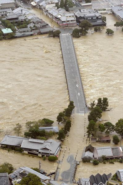The Togetsukyo Bridge is seen just above the Katsura River as the river flooded by torrential rains caused by a powerful typhoon, submerging houses in surrounding residential areas in Kyoto, western Japan, Monday, Sept. 16, 2013. Typhoon Man-yi, one of the most powerful storms to lash Japan this season, was packing wind speeds of 162 kilometres (100 miles) per hour Monday morning and headed toward Tokyo. (AP Photo/Kyodo News) JAPAN OUT, CREDIT MANDATORY