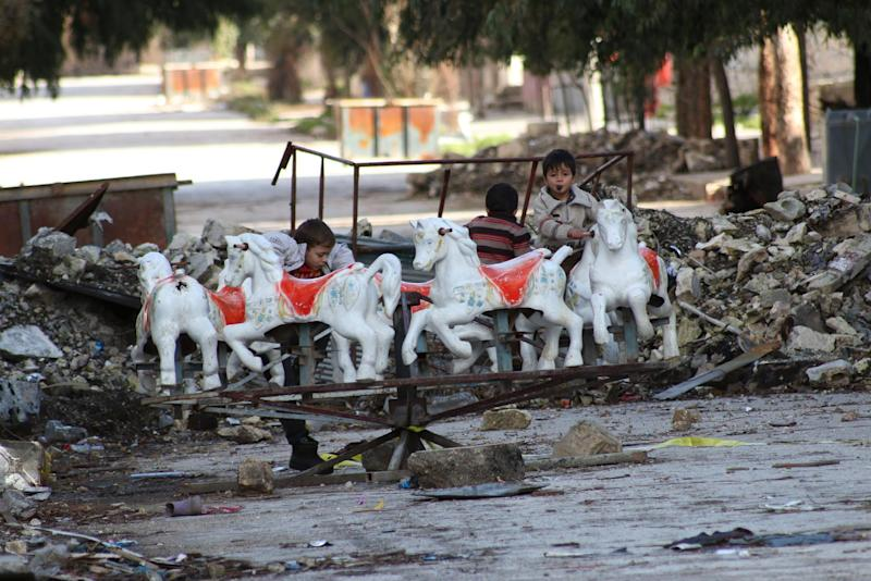 Children play on a damaged carousel in the northern Syrian city of Aleppo on January 8, 2015