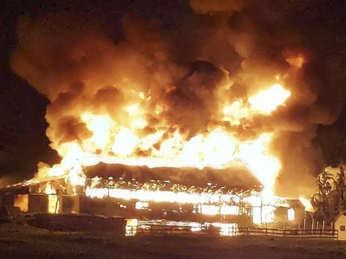 In this image provided by Deanna Raymond, a barn at Scamman Farm, in Stratham, N.H., is engulfed in flames late Monday, May 10, 2021. The fire destroyed the barn at the farm that's been the backdrop for political events for Republican presidents and candidates through the years. (Lucas Dawson via AP)