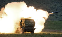 FILE - In this file photo taken May 23, 2011, flames engulf the launch truck as soldiers fire the High Mobility Artillery Rocket System (HIMARS) produced by Lockheed Martin during combat training in the high desert of the Yakima Training Center, Wash. China announced Monday, Oct. 26, 2020, it will impose sanctions on U.S. companies including Raytheon, Boeing and Lockheed Martin for supplying weapons to rival Taiwan, a foreign ministry spokesman said Monday. (The Olympian, Tony Overman via AP, File)