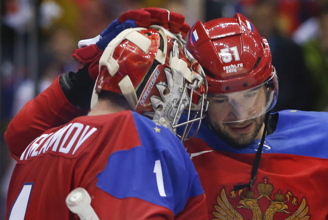Russia defenseman Fyodor Tyutin (51) greets Russia goaltender Semyon Varlamov after Russia defeated Slovenia 5-2 in a men's ice hockey game at the 2014 Winter Olympics, Thursday, Feb. 13, 2014, in Sochi, Russia. (AP Photo/Julio Cortez)