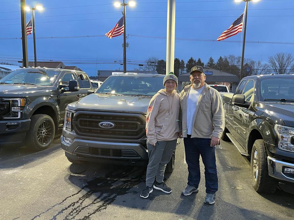 Rodney Boyer (right) stands with his grandson Dominick Boyer at Shults Ford in Wexford, Pennsylvania shortly after buying his new 2021 F-150 XLT in Carbonized Gray. He was the first customer to purchase the redesigned model in the Pittsburgh region. This photo was taken December 3, 2020.