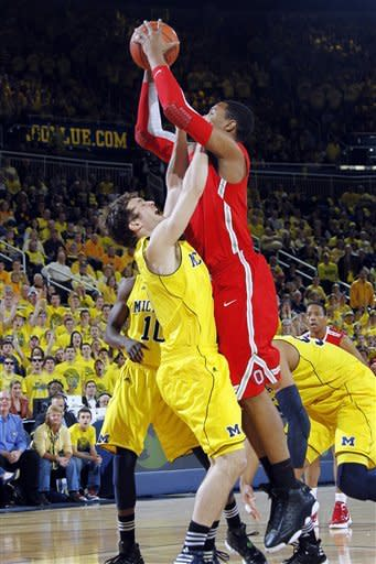 Michigan guard Zack Novak, left, draws a charge from Ohio State forward Jared Sullinger, right, in the first half of an NCAA college basketball game, Saturday, Feb. 18, 2012, in Ann Arbor, Mich. (AP Photo/Tony Ding)
