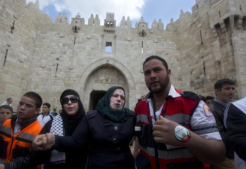 A Palestinian woman reacts after Israeli border police officers sprayed pepper spray during a demonstration marking the Land Day at the Damascus gate in Jerusalem's old city, Sunday, March 30, 2014. The Land Day commemorates the Israeli government expropriation of thousands of dunams of land from Palestinians in 1976. (AP Photo/Sebastian Scheiner)