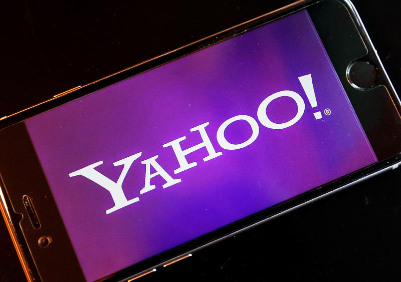 FILE - In this Dec. 15, 2016, file photo, the Yahoo  logo appears on a smartphone in Frankfurt, Germany. In a regulatory filing on Monday, March 13, 2017, Yahoo named the top executives who will lead what's left of the company after its business is sold to Verizon. Current CEO Marissa Mayer will stay at Yahoo until the $4.48 billion Verizon deal closes, expected by the end of June 2017. The filing did not say what will happen to her position after this. (AP Photo/Michael Probst, File)