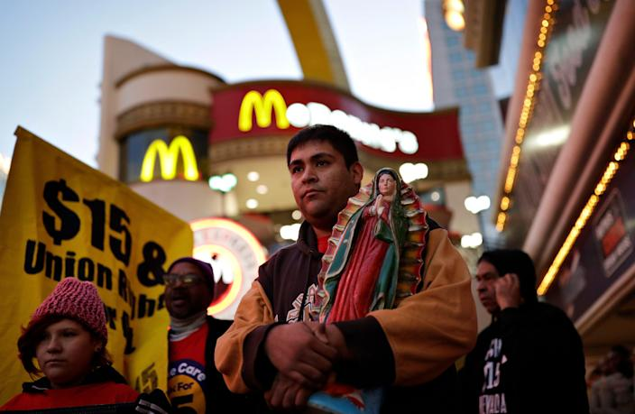 Martin Macias-Rivera holds a statue as he and others protest near a McDonald's restaurant along the Las Vegas Strip, Tuesday, Nov. 29, 2016, in Las Vegas. The protest was part of the National Day of Action to Fight for $15. The campaign seeks higher hourly wages, including for workers at fast-food restaurants and airports.