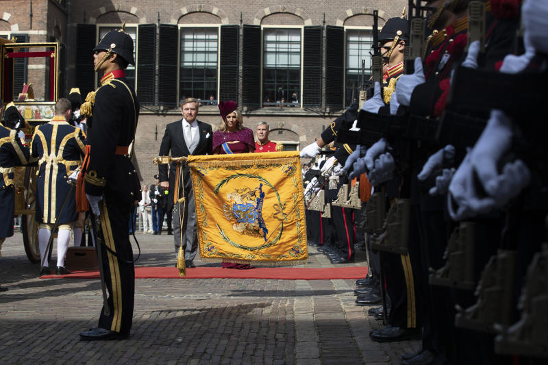 Dutch King Willem-Alexander and Queen Maxima salute the coat of arms after arriving in a horse-drawn carriage outside the Knight's Hall in The Hague, Netherlands, Tuesday, Sept. 17, 2019, for a ceremony marking the opening of the parliamentary year with a speech by King Willem-Alexander outlining the government's budget plans for the year ahead. (AP Photo/Peter Dejong)