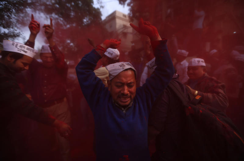 Supporters of new political party called Aam Aadmi Party, or Common Man's Party celebrate outside the party office in New Delhi, India, Sunday, Dec. 8, 2013. Aam Aadmi Party played spoiler in the race and pushed Congress into third place, according to early results. (AP Photo/Saurabh Das)