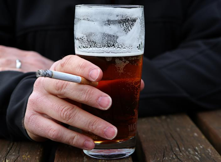 A man holds a cigarette and a pint of beer.