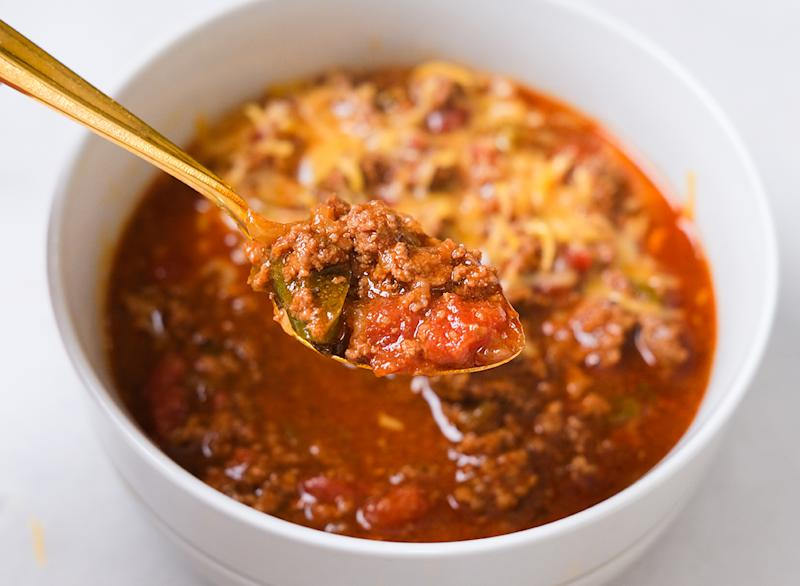 spoon holding up chili from a bowl