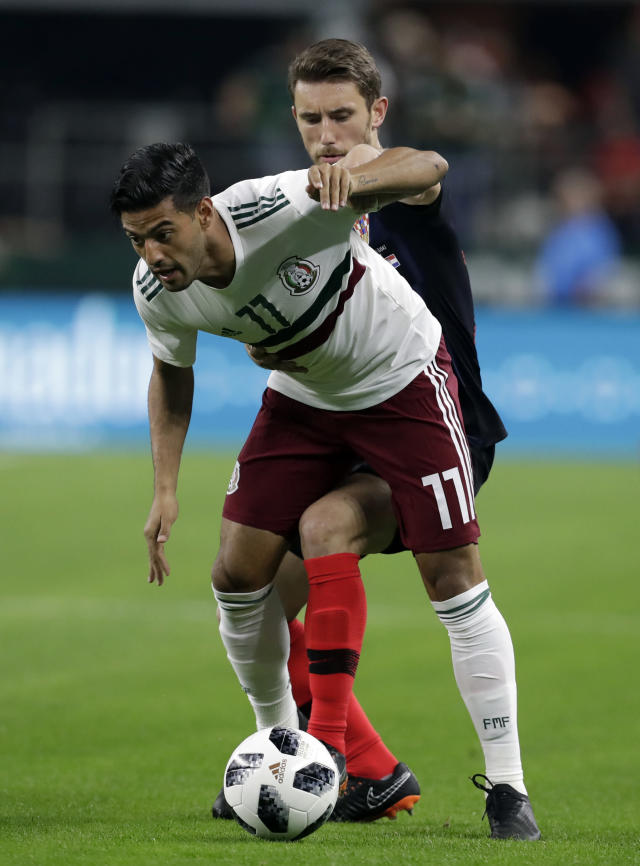 Mexico forward Carlos Vela, front, and Croatia forward Josip Pivaric, rear, compete for control of the ball in thee first half of a friendly soccer match in Arlington, Texas, Tuesday, March 25, 2018. (AP Photo/Tony Gutierrez)