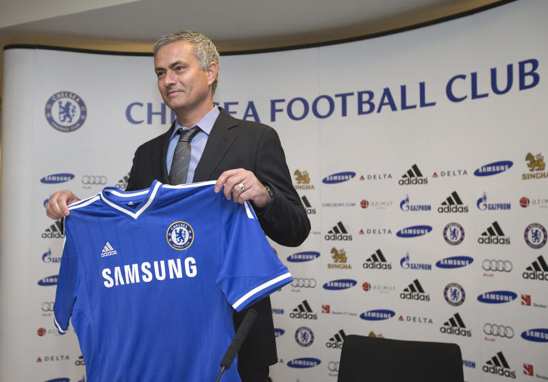 Chelsea's new manager Jose Mourinho holds up the team shirt as he poses for photographers at the start of a press conference at Chelsea's Stamford Bridge stadium in London, Monday June 10, 2013. Mourinho has been reappointed coach of Chelsea for the second time. (AP Photo/Alastair Grant)